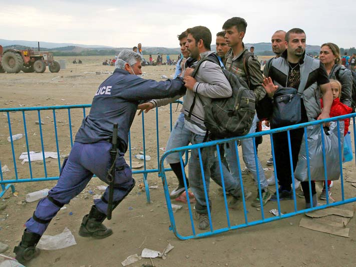 A Greek policeman pushes refugees behind a barrier at Greece's border with Macedonia, near the Greek village of Idomeni. (© Yannis Behrakis/Reuters)