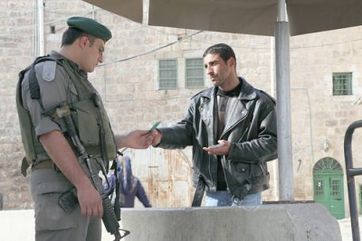 An Israeli soldier checks the Israeli-issued ID card of a Palestinian at one of the many checkpoints within the city of Hebron.   (© Photo: Rich Wiles/BADIL, 2012)