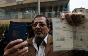 A Palestinian refugee from the Syrian refugee camp of Yarmouk holds up his passport in front of the United Nations Relief and Works Agency (UNRWA) offices in the Cola district of the Lebanese capital, Beirut, on 19 December 2012. (Source: al-akhbar.com)