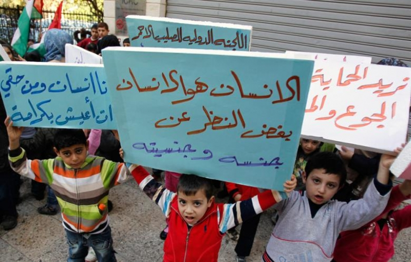 Palestinian children who were living in Yarmouk Palestinian refugee camp before fleeing Syria, hold banners during a protest in front of the International Committee of the Red Cross (ICRC) in Beirut 17 January 2013. (Source: al-akhbar.com)
